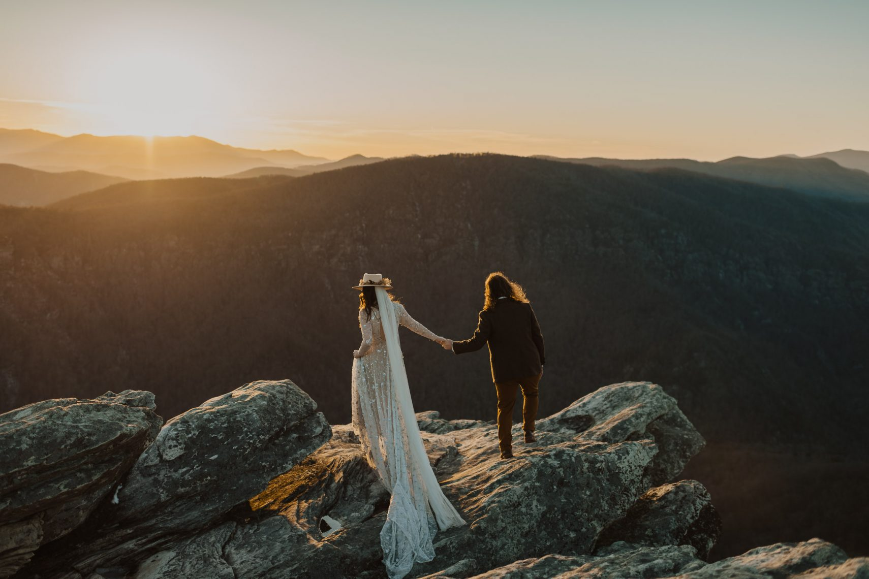 couple hiking at sunset to the top of a mountain.