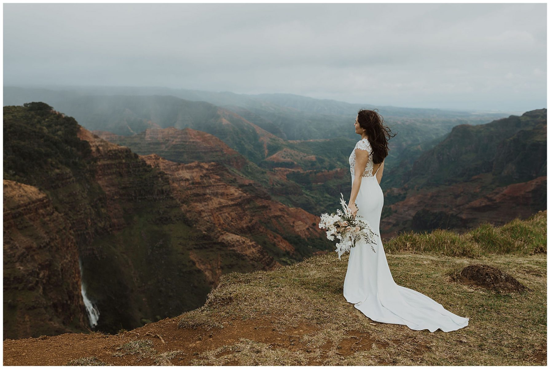 bride standing on the cliffs of Waimea Canyon in Kauai, Hawaii holding a white bouquet