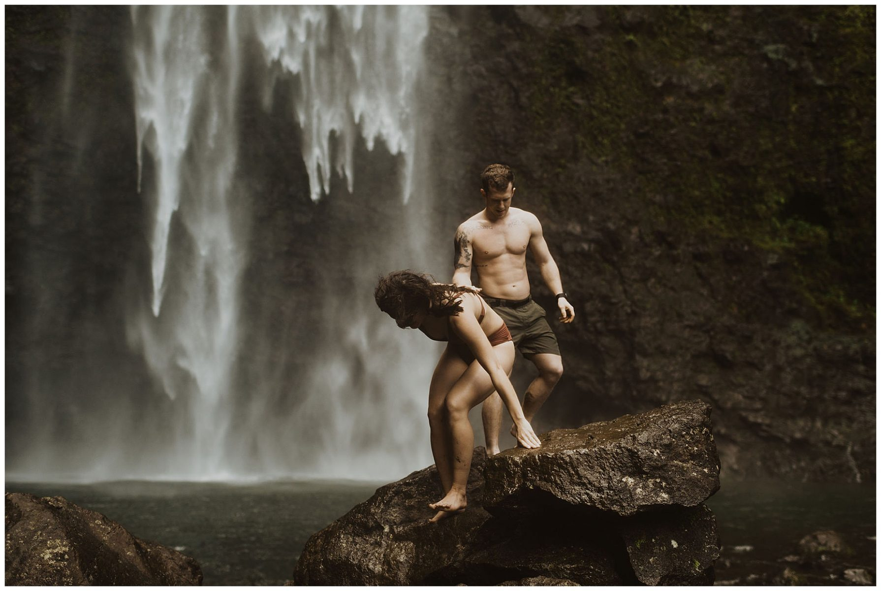 couple swimming and playing in a waterfall in kauai, hawaii
