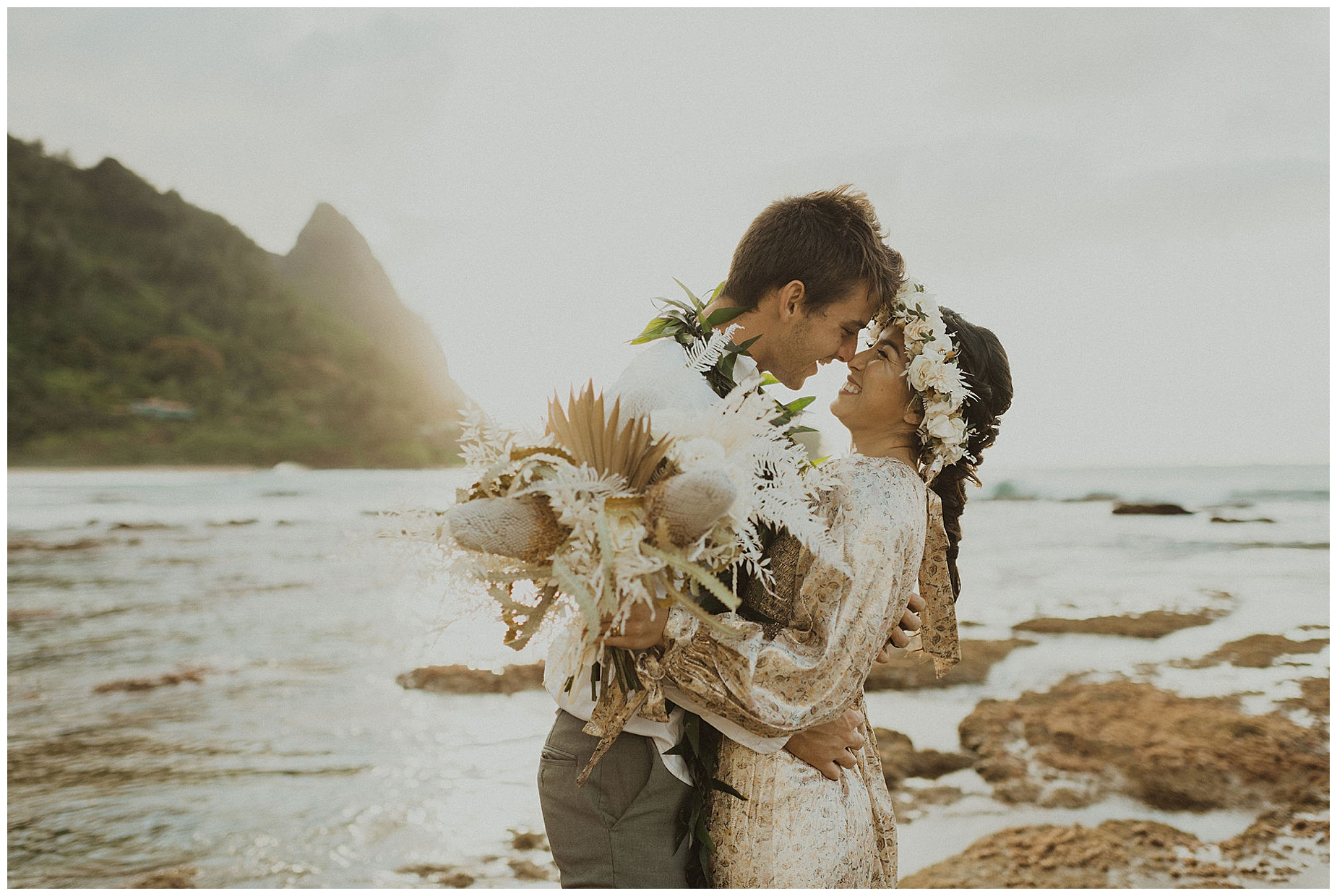 bride dressed in a gold dress holding her boho dried bouquet and wearing a white flower crown on the beach of kauai during her beach elopement in hawaii
